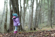 a little girl in a forest looking up