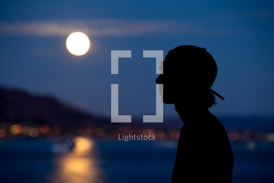 silhouette of a teen boy under moonlight