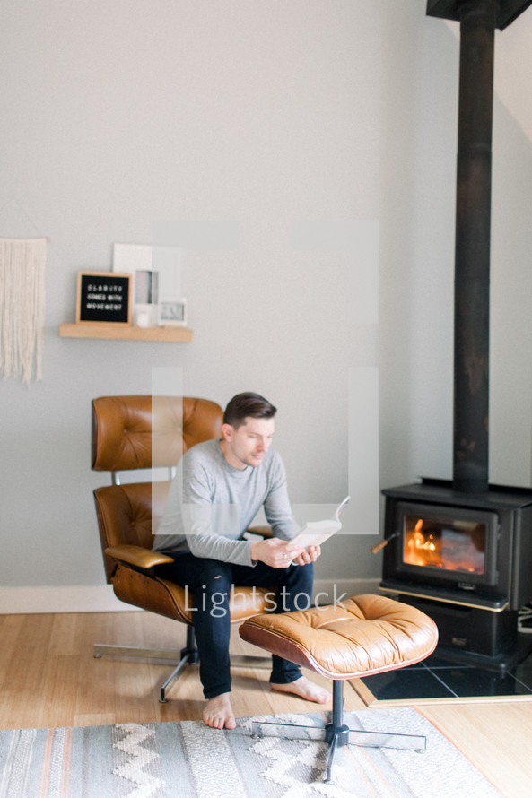 a man sitting in a leather chair reading a Bible