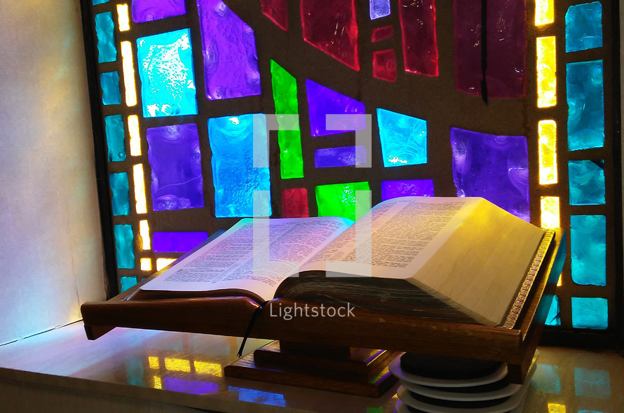 The Living Word of God open to the scripture passages in front of a stained glass window surrounded by sunlight and reflecting light prism ready to be read and alive and powerful for all those who hear and head the word of God.