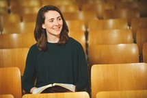 a woman reading a Bible alone in a church smiling