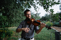 man playing a fiddle outdoors