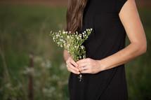Woman in field holding bouquet of wild flowers