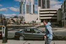 man walking on a sidewalk in front of a parking meter