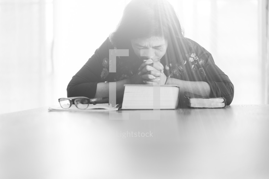 a woman sitting praying over a Bible