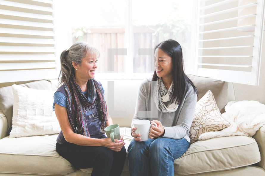 Asian women sitting on a couch talking and holding mugs