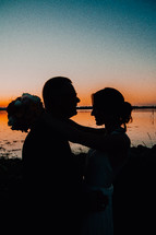 silhouette of a bride and groom at sunset