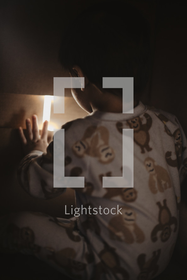 a toddler boy in pajamas and a nightlight