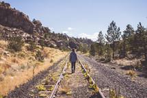 a woman walking down abandoned train tracks
