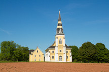 plowed field and church