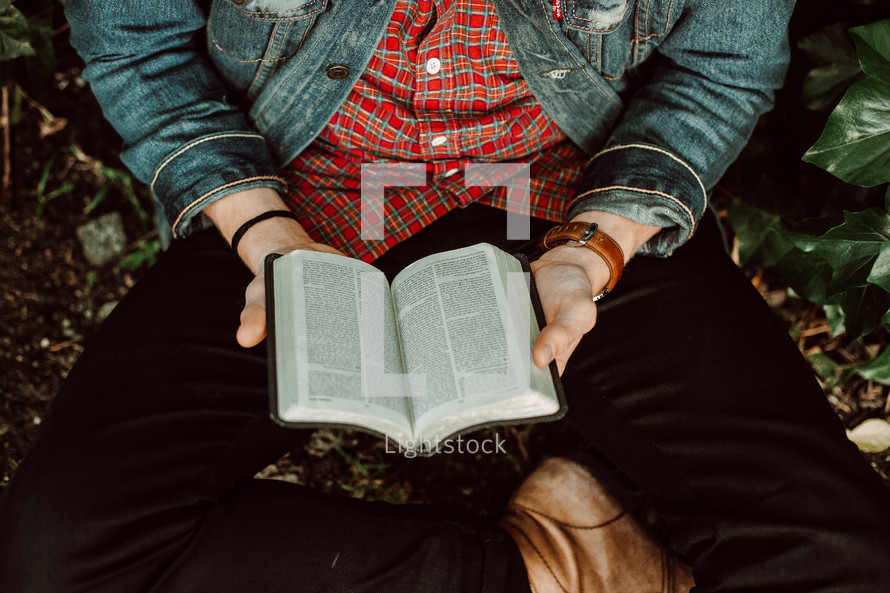 a young man sitting reading a Bible in his lap