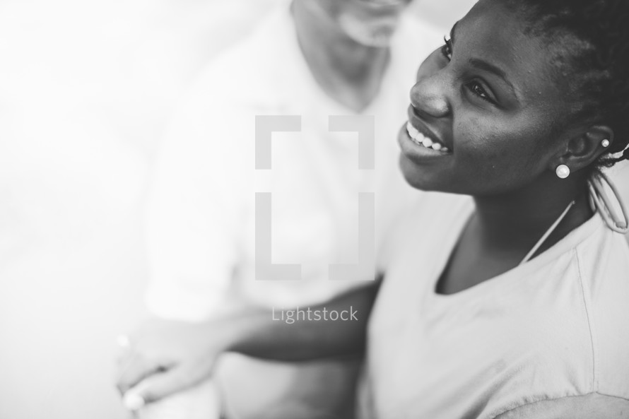 Smiling girl holding a man's arm.