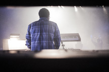 A shot from behind of a keyboardist during corporate worship