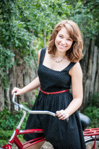 a young woman in a polka dot dress on a red beach cruiser bicycle