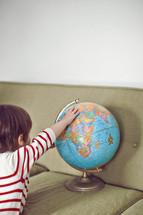 boy toddler touching a globe