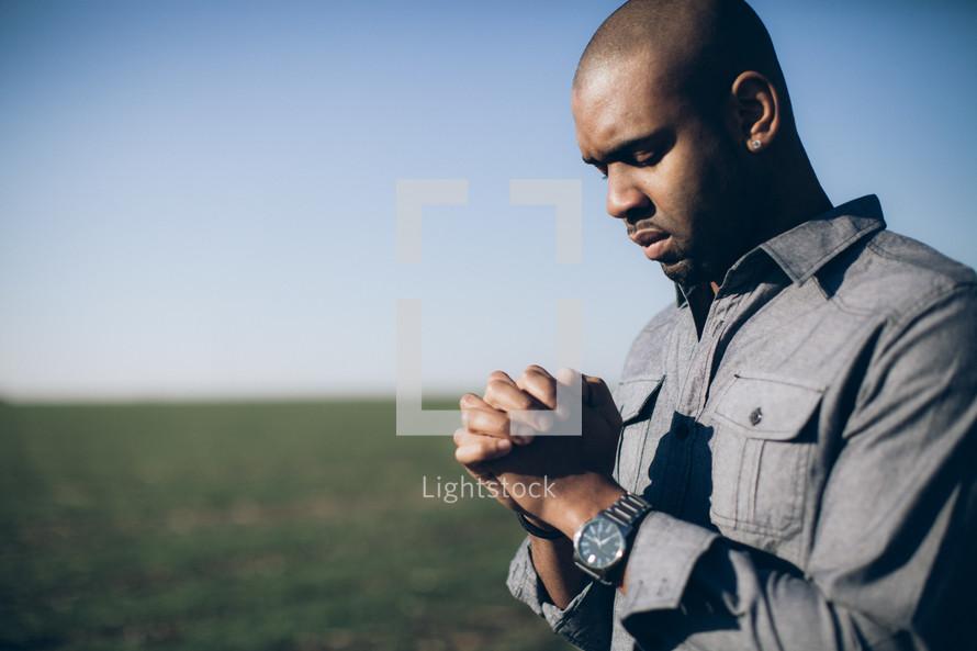 man in prayer in a field
