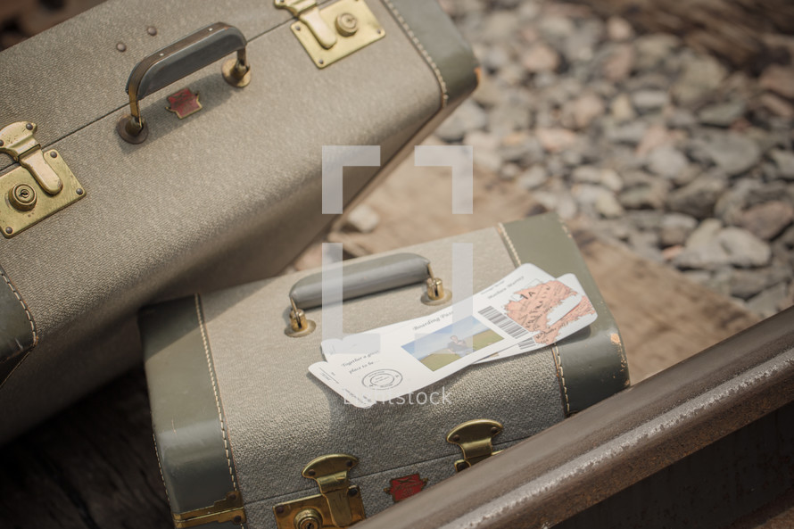 tickets and luggage on railroad tracks