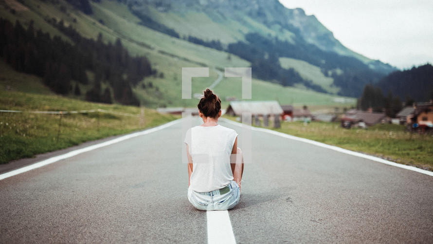 a young woman sitting in the middle of a rural street