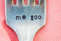the words me too engraved stamped into a dinner fork sitting on a pink linen