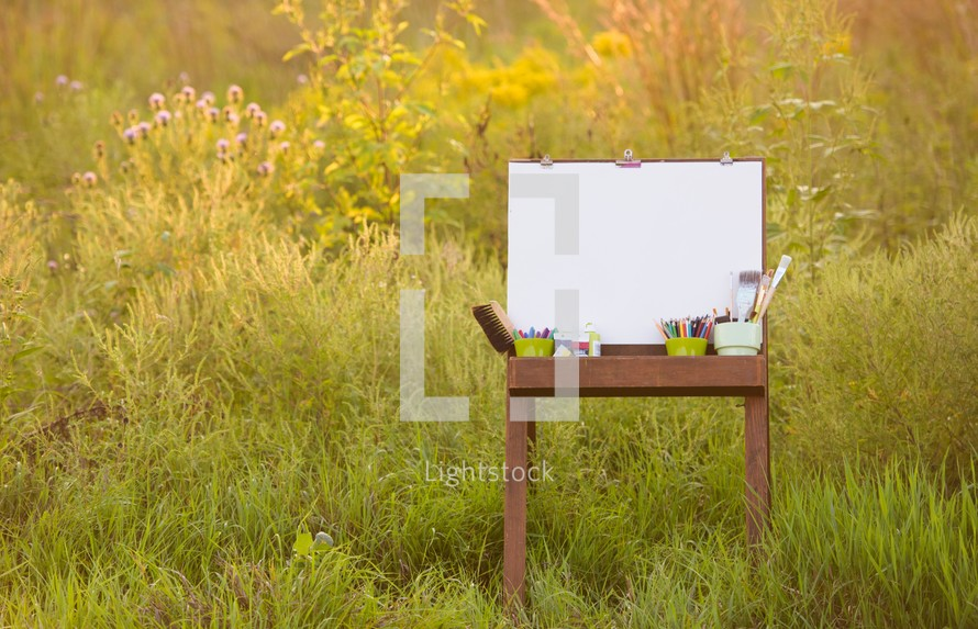 easel, art supplies, and a blank canvas outside