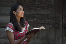 Woman holding Bible in front of wooden doors.