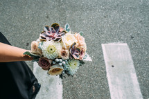 A floral bouquet held by a woman in a parking lot.