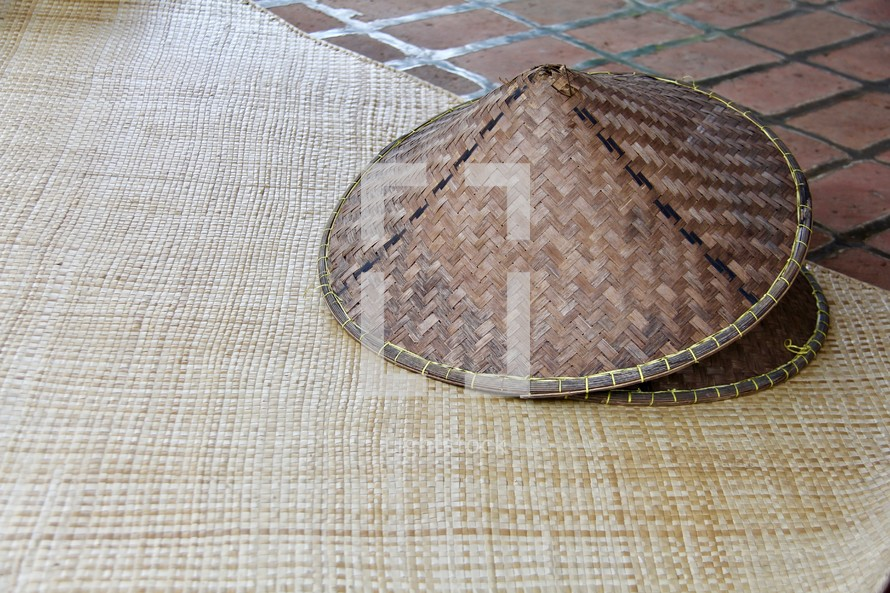 straw hats on a straw mat background traditional eastern oriental