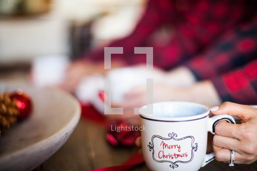 People sitting at a table at a Christmas party with a coffee mug