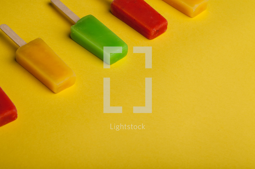 Brightly colored popsicles lined up on a yellow background.