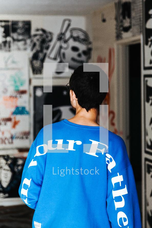 man looking at a graffiti covered wall