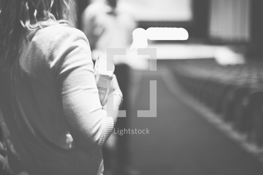 woman carrying a Bible into a church