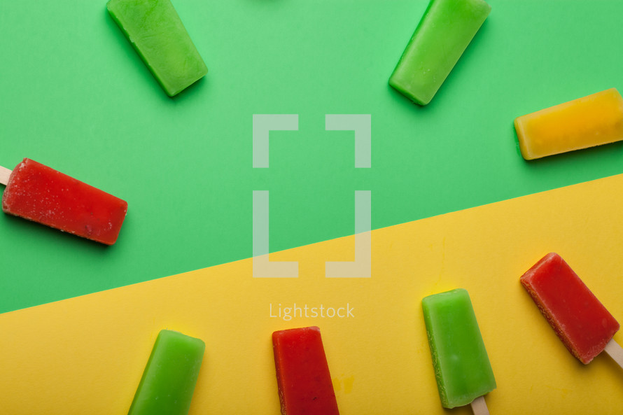 Brightly colored popsicles in a circle on a green and yellow background.