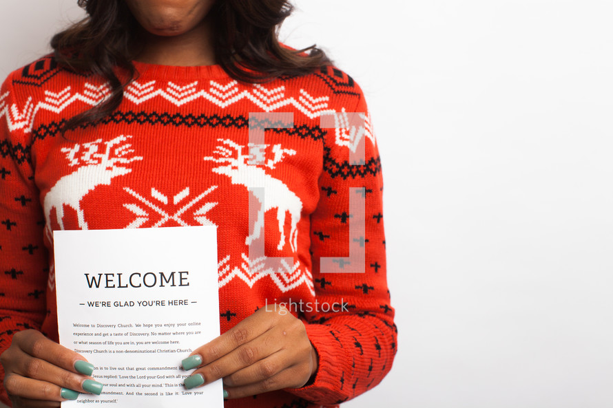 woman in an ugly Christmas sweater holding an invitation