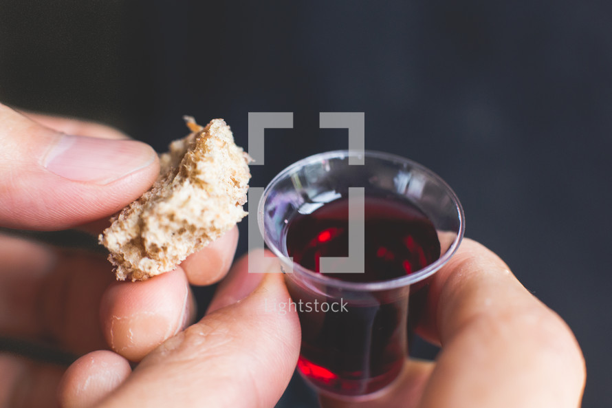 communion wine cup and bread in a man's hands