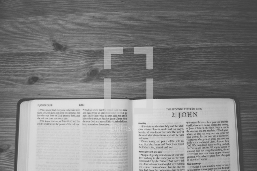 Bible on a wooden table open to the book of 2 John.