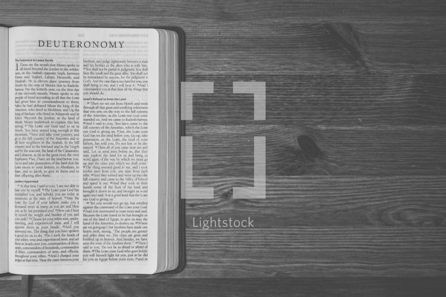 Bible on a wooden table open to the book of Deuteronomy.