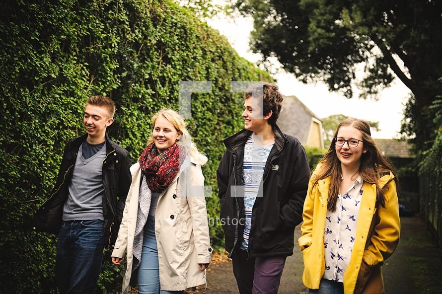 youth walking on a sidewalk in coats
