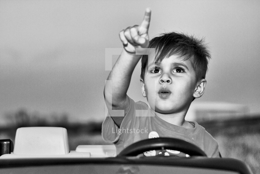 Boy in a toy car pointing at the sky