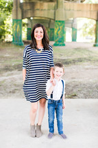 a mother and son standing under a bridge