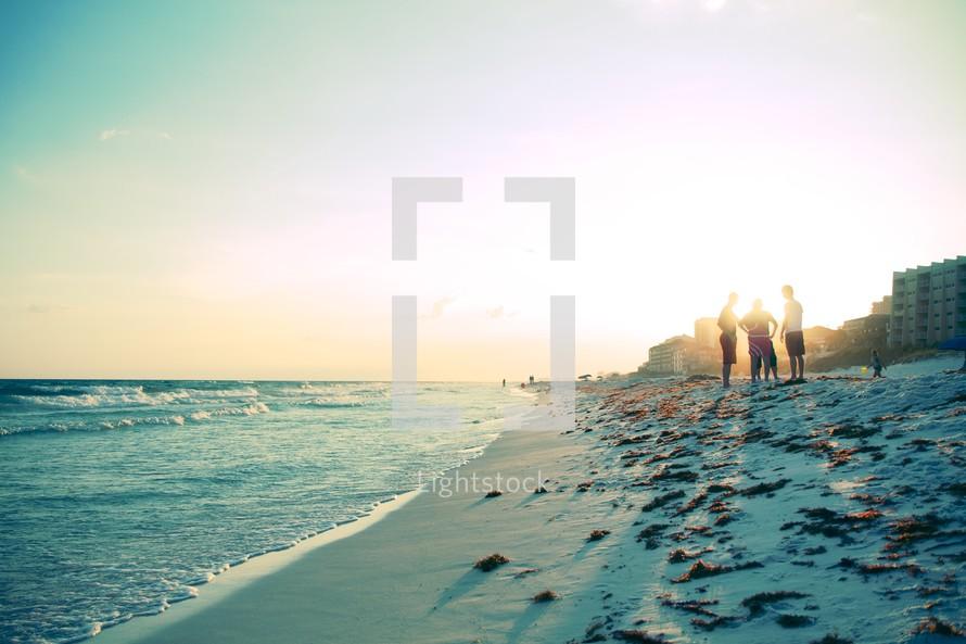 Guys standing on the seashore at sunset