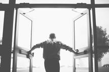 man holding open double doors