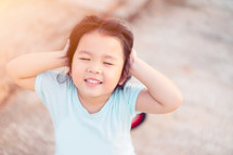 a little girl covering her ears