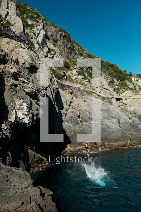 A bunch of people jumping off a cliff into the water