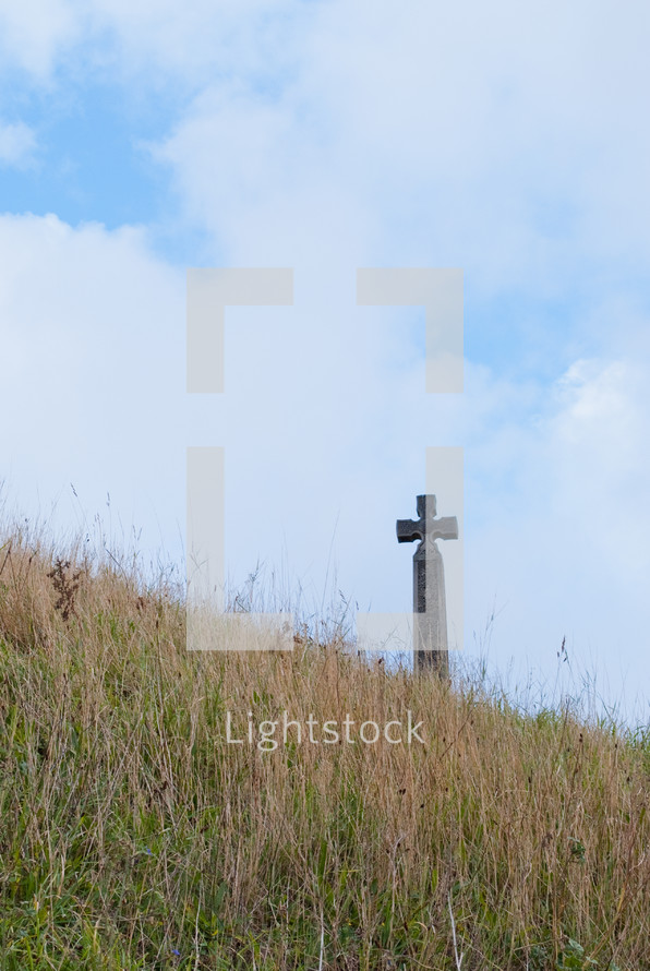 A cross in a field of grass against a blue sky.