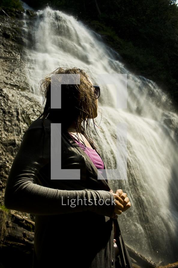 woman looking up at a waterfall