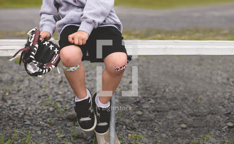 boy child sitting on a bench holding a baseball glove with band-aides on his knees