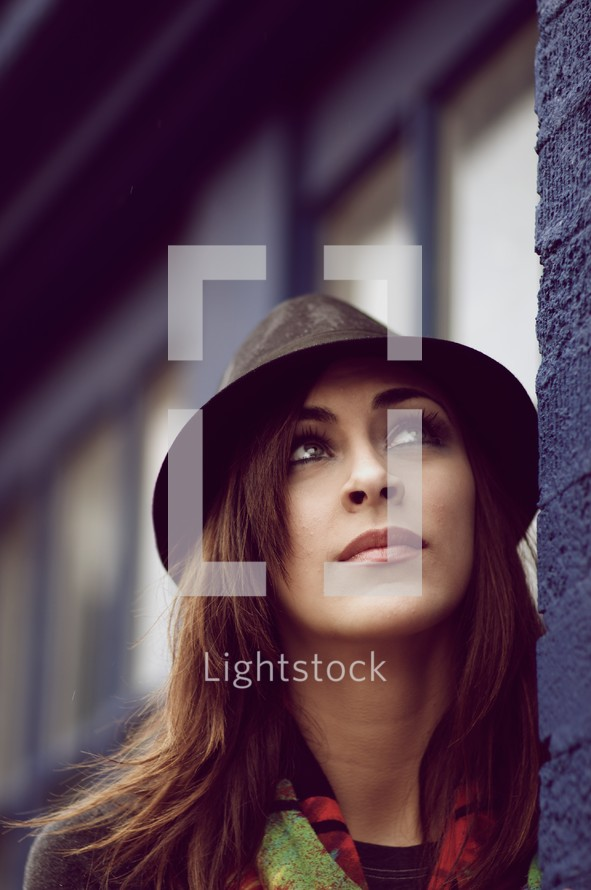 A college-aged woman with brown hair looking up - pondering, thinking