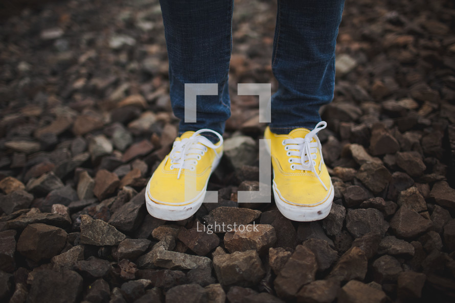 yellow sneakers standing on the gravel