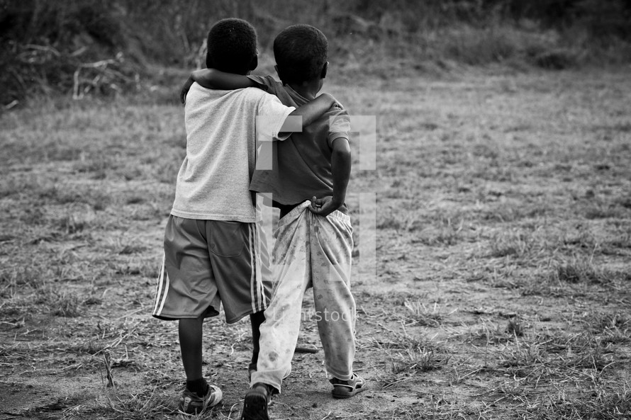 Two young boys walking together with their arms around each other