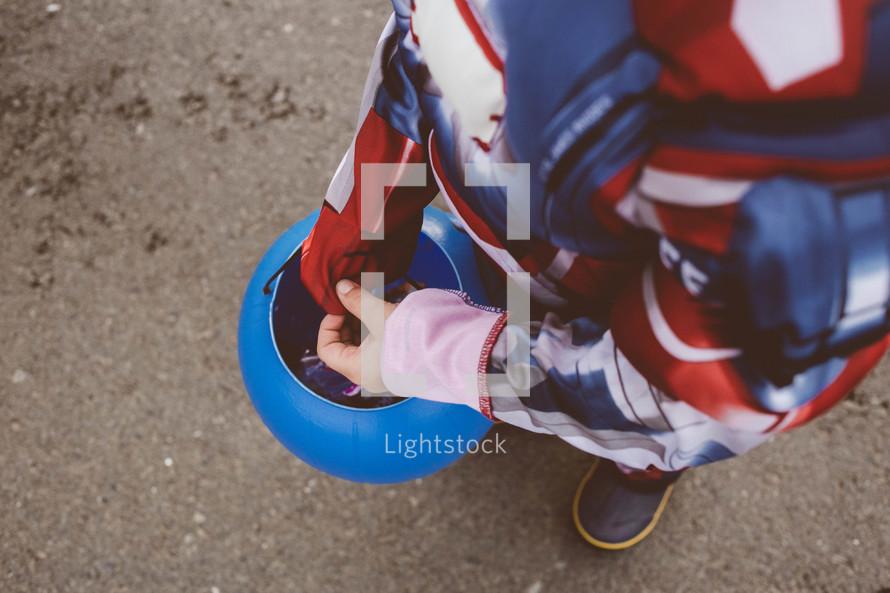 boy child holding a jack-o-lantern trick-or-treating